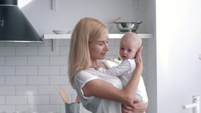 爱的母亲在手新生儿女孩,年轻女人拥抱和亲吻她的厨房的孩子画象轻轻地举行  股票视频