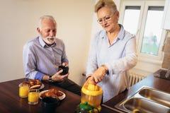 爱的资深夫妇获得准备在早餐的乐趣健康食品在厨房 免版税库存照片