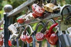 爱红色锁在桥梁垂悬作为幸福和老婚礼传统的标志 库存照片