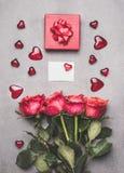 爱组成与红色礼物盒、丝带、玫瑰束、空白白皮书卡片和心脏,顶视图的标志 库存照片
