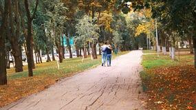 爱走在秋天胡同的夫妇、男孩和女孩 免版税图库摄影
