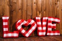 爱长毛绒红色信件的词在木背景的 免版税库存照片