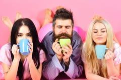 爱饮料咖啡的恋人在床上 三倍在上午放松用咖啡 恋人概念 男人和妇女国内的 免版税库存图片