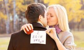 爱,关系,订婚和婚礼概念-人提出妇女结婚,红色箱子圆环,愉快浪漫夫妇亲吻 库存照片