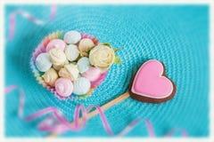 爱,华伦泰` s天、心形的桃红色姜饼曲奇饼在绿松石背景和柔和的淡色彩的标志 免版税库存照片