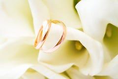 爱,家庭,庆祝,仪式概念-婚礼标志与水芋属白花的两个金黄圆环 免版税库存照片