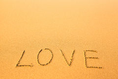 爱-在沙子用手写的文本在海滩,海 库存图片