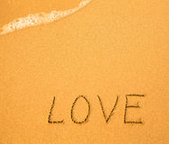 爱-在沙子用手写的文本在海滩 图库摄影