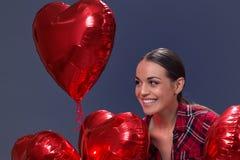爱-微笑与红色心形的气球的妇女 免版税库存照片
