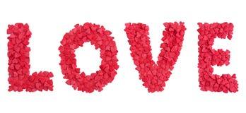爱从心脏糖果的词形状洒在白色 库存图片