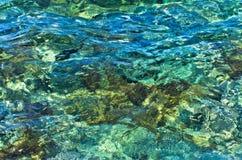 爱琴海岩石海底可看见的通过透明的绿松石水  图库摄影