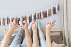 爱-由爱恋的夫妇的手指制成 美好的对在床上放置 库存图片