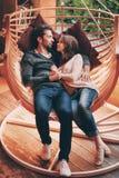 爱说谎在吊床的一对富感情的年轻夫妇的画象看微笑 浪漫男人和妇女庭院 免版税库存照片