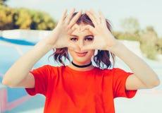 爱 画象微笑的愉快的年轻红头发人妇女,做心脏标志,标志用手 正面人的情感表示感觉 库存图片