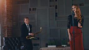 爵士乐二重奏在餐馆阶段执行  妇女唱歌在话筒 萨克斯管吹奏者 股票视频