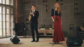 爵士乐歌唱者在阶段执行与萨克斯管吹奏者在黑衣服 二重奏 音乐 影视素材