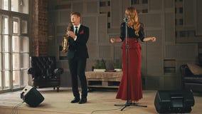 爵士乐歌唱者在阶段,黑衣服的萨克斯管吹奏者的点击手指使用 二重奏 股票视频