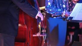 爵士乐音乐会在音乐厅里 一个人弹大提琴的和唱歌在背景的歌唱者 影视素材