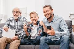 父亲、儿子和祖父一起坐长沙发在拿着数字式片剂,智能手机的客厅 库存图片