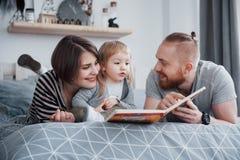 父亲、母亲和一点女儿读书儿童` s在一个沙发预定在客厅 愉快的大家庭读了  免版税库存照片