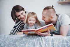 父亲、母亲和一点女儿读书儿童` s在一个沙发预定在客厅 愉快的大家庭读了  免版税库存图片