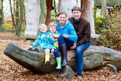 父亲、母亲和两个小孩坐一条长凳在秋天 图库摄影
