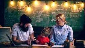 父亲、母亲和他们的儿子油漆在学校课程 概念了解 制服的小学生 教师在教室 股票录像