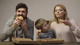 父亲、母亲和他们的小儿子吃在白色背景隔绝的可口比萨 家庭享用一可口比萨 股票录像