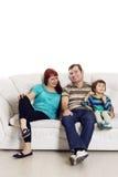 父亲、母亲和儿子坐沙发 免版税库存照片