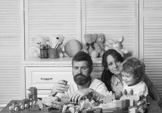 父亲、母亲和儿子游戏室的在轻的木背景 父母和孩子与被集中的面孔做砖 免版税库存图片
