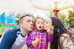 父亲、母亲和女儿吹的泡影,在娱乐的家庭 免版税库存图片
