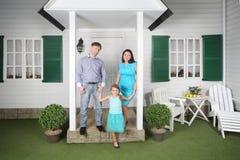 父亲、母亲和女儿站立近的门廊 图库摄影
