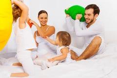 父亲、母亲和孩子使用与五颜六色的枕头 免版税库存照片