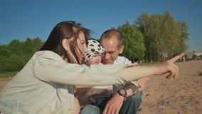 父亲、母亲和小女儿一起坐在湖岸的沙子 他们愉快地谈并且享受在a的自然 股票录像