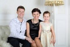 父亲、母亲和小逗人喜爱的女儿微笑 免版税库存照片