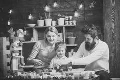 父亲、母亲和逗人喜爱的儿子使用与建设者砖 在繁忙的面孔的家庭在游戏室一起花费时间 库存图片