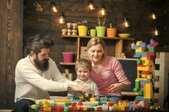 父亲、母亲和逗人喜爱的儿子使用与建设者砖 演奏玩具的孩子 在繁忙的面孔的家庭花费时间 库存图片
