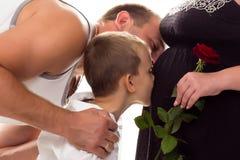 父亲亲吻的怀孕的儿子肚子 免版税库存图片