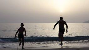 父亲人男孩sousing在日落海的太阳潜水剪影  股票视频