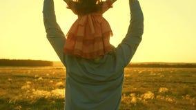 父亲使用与他的他的肩膀的女儿在日落光芒  爸爸继续他心爱的孩子肩膀  影视素材
