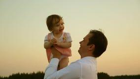 父亲使用与他的女儿在公园 爸爸投掷他的天空的婴孩 有父母的愉快的童年孩子 股票录像