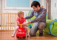 年轻父亲使用与女儿 爸爸教他的孩子驾驶玩具汽车 免版税库存照片