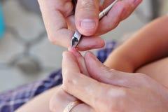 父亲切口有指甲夹的小孩的指甲盖 免版税库存照片