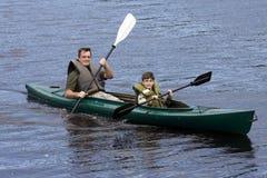 父亲划皮船的儿子 库存图片