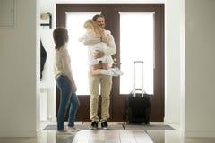 父亲到达了来了在家返回在举行拥抱的旅行以后da 库存照片