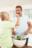 父亲厨房现代准备的沙拉儿子 免版税库存照片