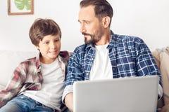 父亲和一点儿子在家坐沙发使用膝上型计算机快乐的特写镜头 免版税图库摄影