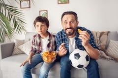 父亲和一点儿子在家坐紧张沙发吃芯片藏品球观看的足球 免版税图库摄影
