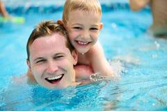 年轻父亲和一点儿子游泳在水池 免版税库存图片