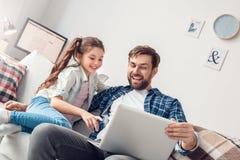 父亲和一点女儿在家观看的动画片坐膝上型计算机笑 免版税库存图片